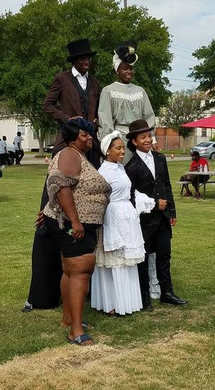 Park visitors pose for pictures with young people in their 19th-century Sunday best.