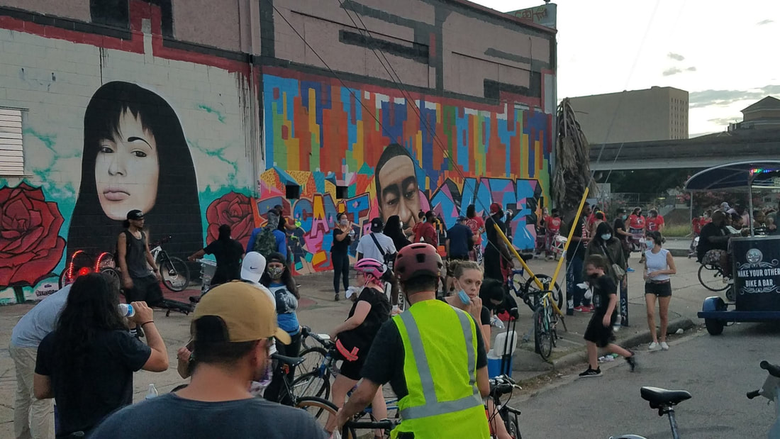 Juneteenth cyclists stop the ride to gather at the George Floyd mural in EaDo, next to a mural of Selena Quintanilla.