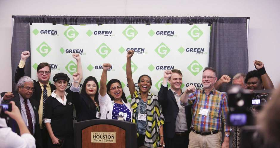 Chronicle photo of ten Green Party candidates with fists raised at a press conference during the Green Party's 2016 national convention at the University of Houston.