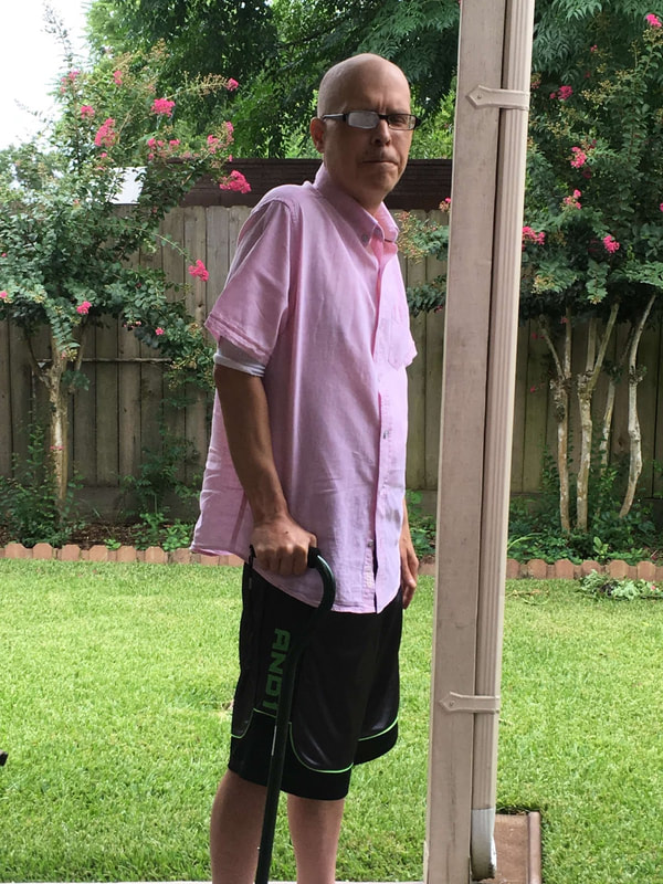 Photo of blogger Harry Hamid in a back yard, wearing a pink guayabera shirt and clutching his walking cane.